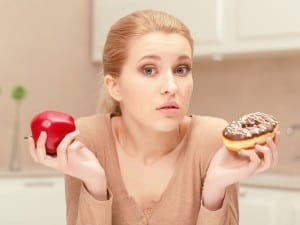 Being in doubt. Nice young blonde woman in her kitchen sits holding apple in one hand and donut in another hand hesitating and trying to choose what she has to eat